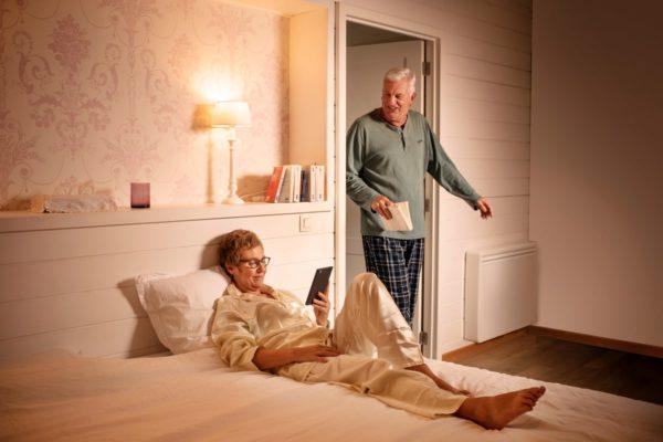 couple senior dans leur chambre avec un radiateur a inertie