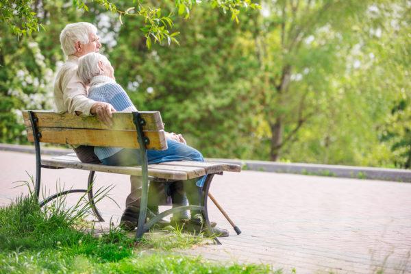 Couple de seniors assis sur un banc dans la nature.