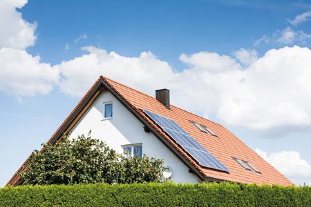 Maison avec des panneaux solaires sur le toit.