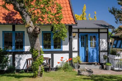 Maison aux volets bleus avec jardin.