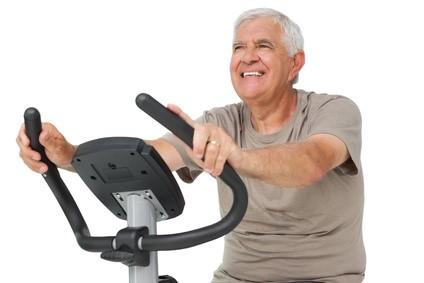 Senior heureux sur un vélo d'appartement