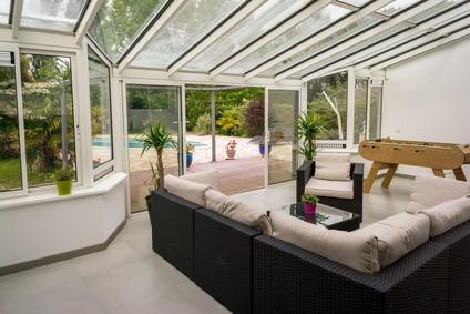 Salon d'été dans une véranda et piscine.